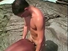 Twink does African male on sea shore