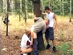Triple boys kiss each other outdoors
