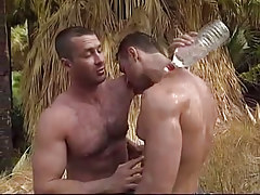 Muscle homosexual dilfs stroke each other in jungle