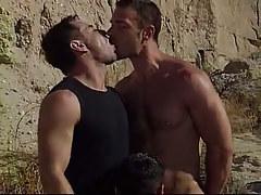 Cute gay guy stallion serves two dilfs in desert